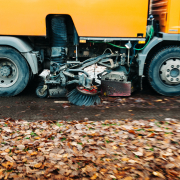 In motion orange street sweeper truck on the street working cleaning autumn foliage